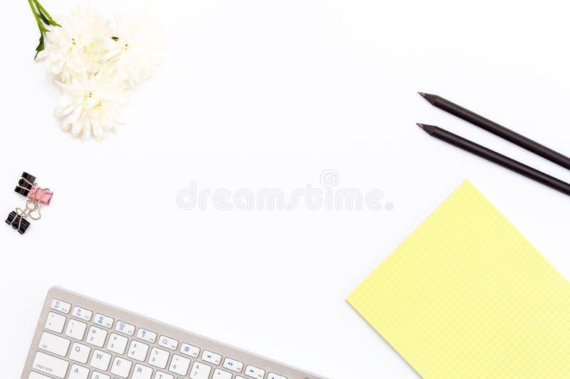 Toetsenbord, een geel stootkussen, een zwart potlood twee, een chrysantenbloem en klemmen voor document op witte achtergrond Vlak royalty-vrije stock foto's
