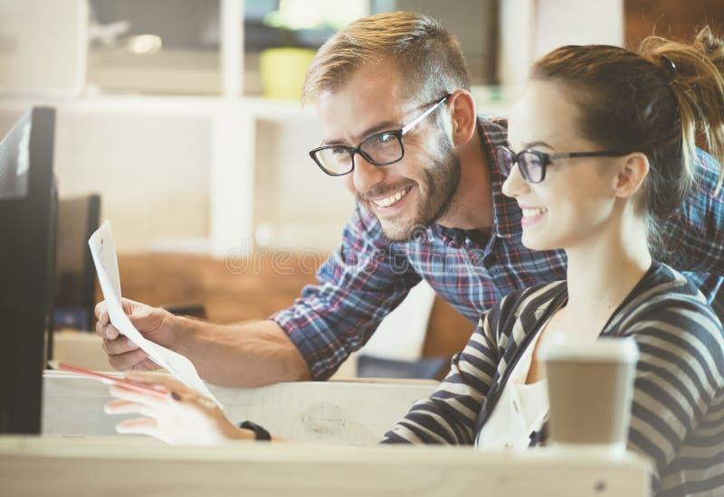 Toevallig bedrijfspaar die computer in het bureau met behulp van Twee collega's die samenwerken royalty-vrije stock afbeeldingen