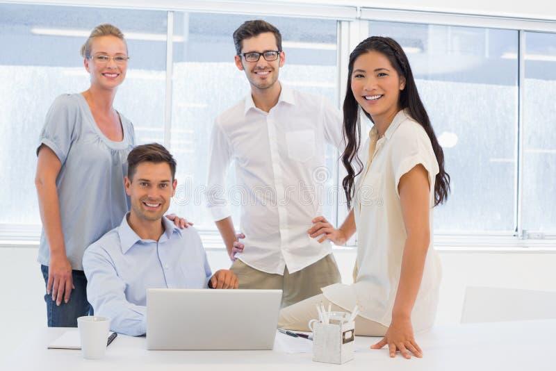 Toevallig commercieel team die bij camera bij bureau glimlachen stock foto's
