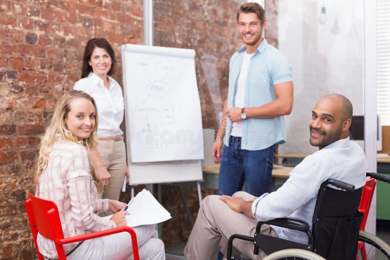 Toevallig commercieel team die een vergadering hebben die bij camera glimlachen stock afbeelding