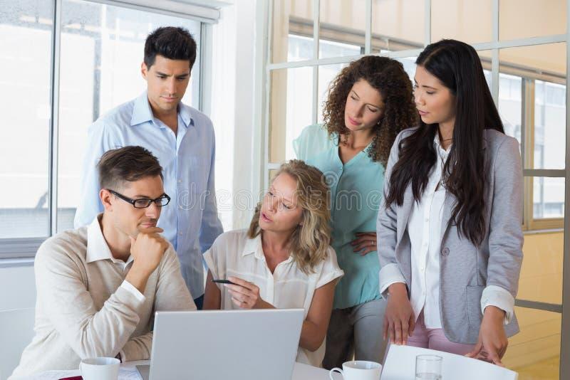 Toevallig commercieel team die een vergadering hebben die laptop met behulp van stock foto