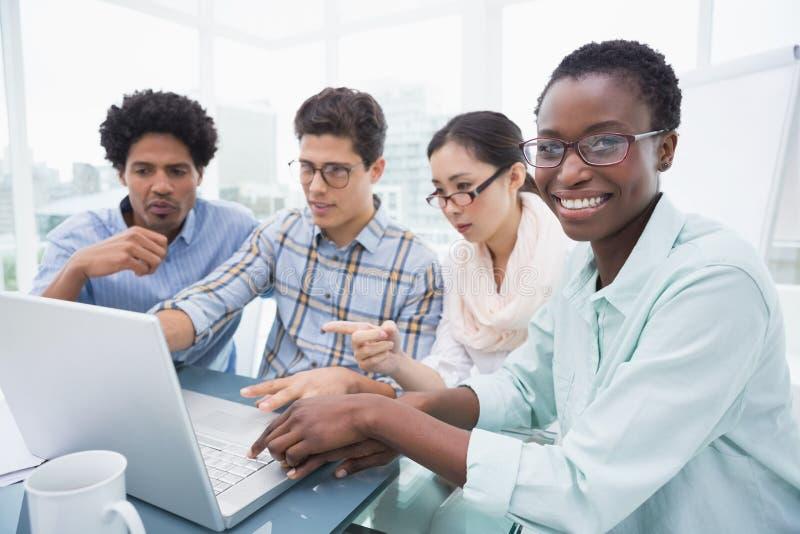 Toevallig commercieel team die een vergadering hebben die laptop met behulp van royalty-vrije stock afbeelding