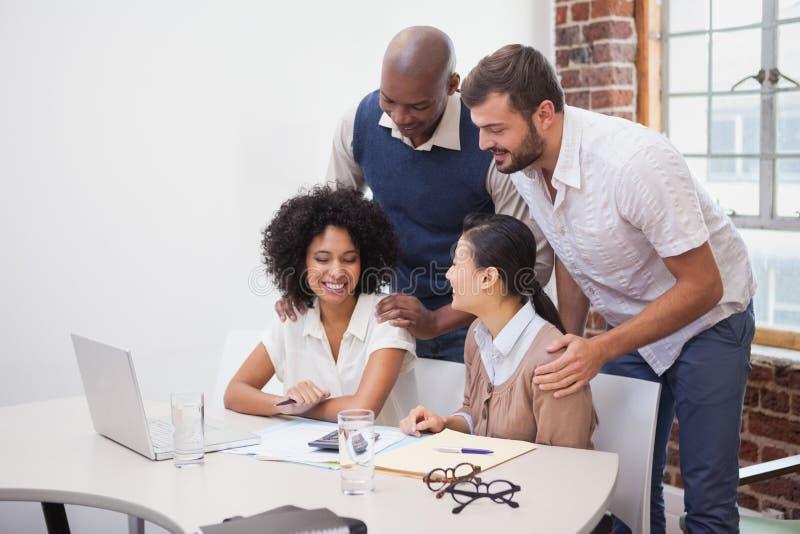 Toevallig commercieel team die een vergadering hebben die laptop met behulp van royalty-vrije stock fotografie
