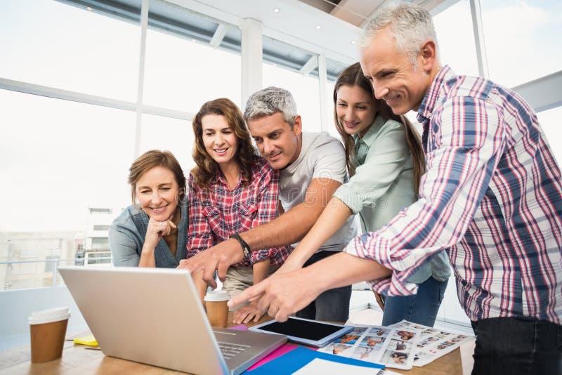 Toevallig commercieel team die een vergadering hebben die laptop met behulp van stock fotografie