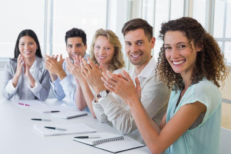 Toevallig commercieel team die en bij camera glimlachen toejuichen stock foto