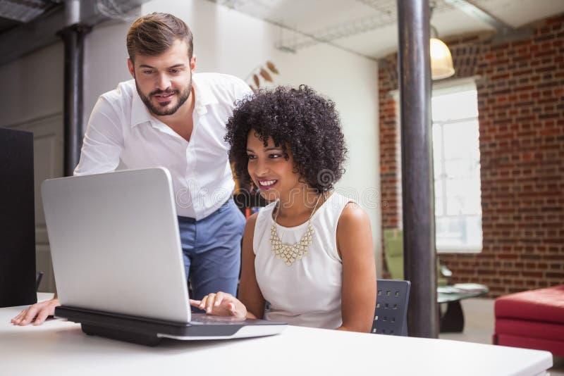 Toevallig commercieel team die laptop samen bekijken royalty-vrije stock afbeelding