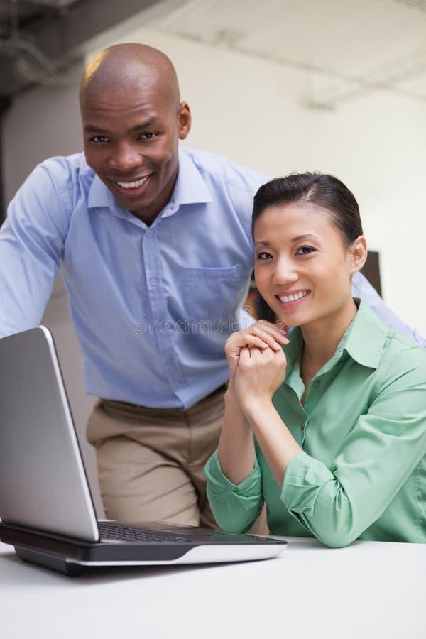 Toevallig commercieel team die samen met laptop werken stock afbeeldingen