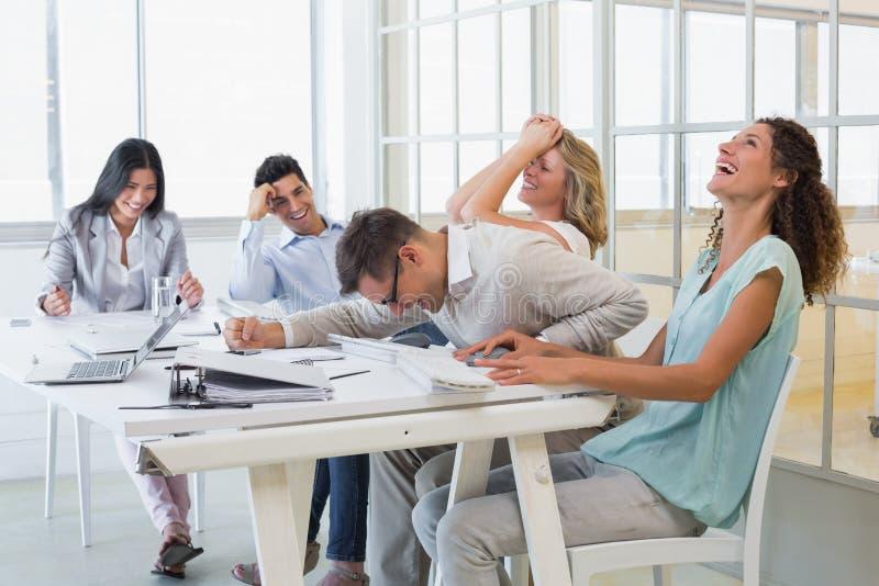 Toevallig commercieel team die tijdens vergadering lachen stock foto's