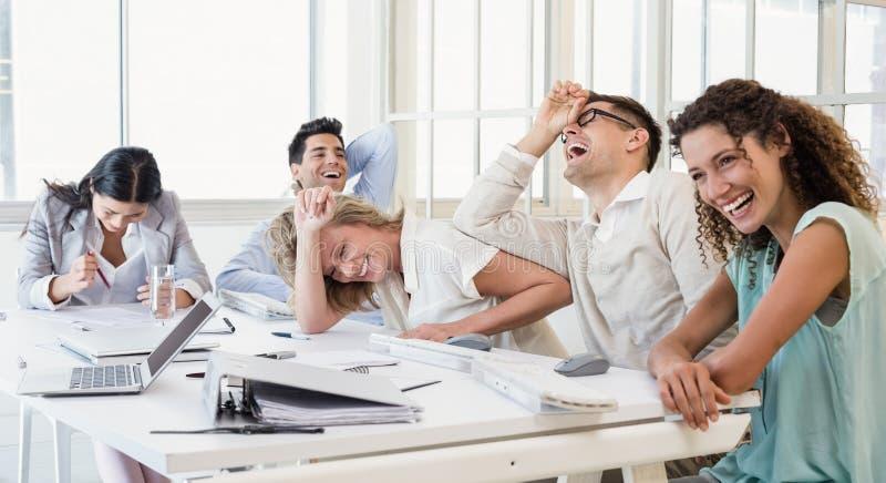 Toevallig commercieel team die tijdens vergadering lachen stock afbeelding