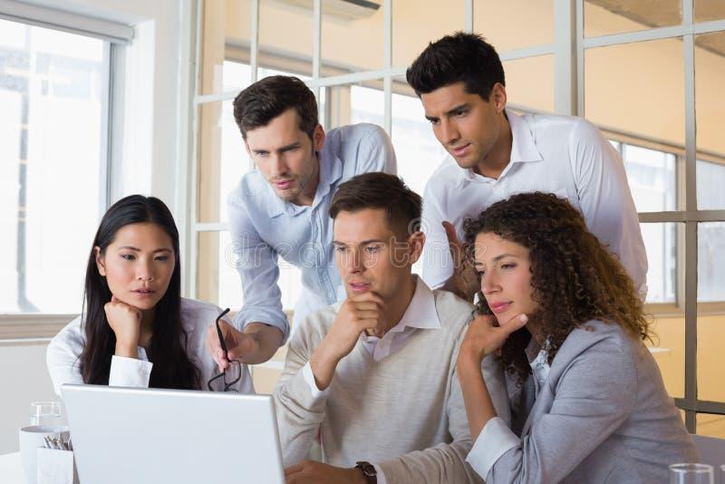 Toevallig glimlachend commercieel team die een vergadering hebben die laptop met behulp van stock afbeelding