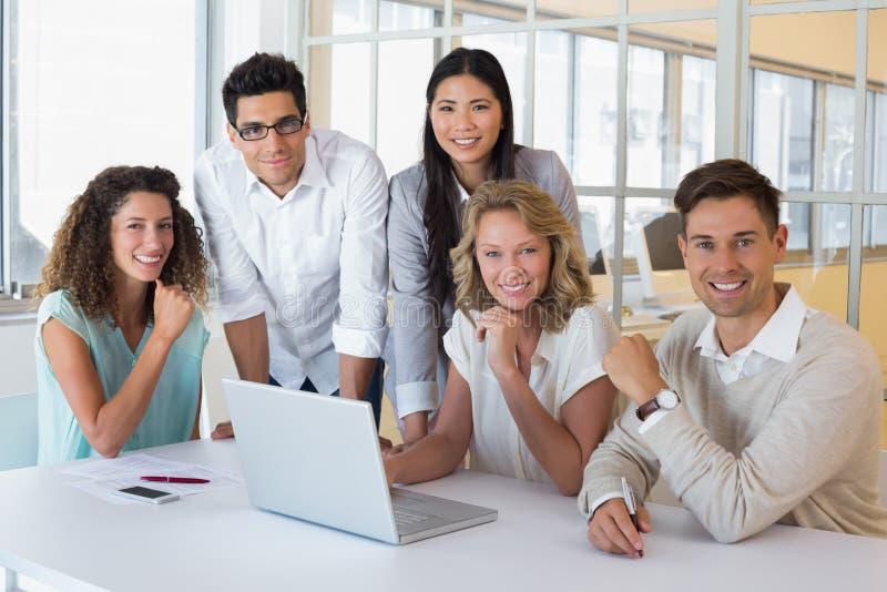 Toevallig glimlachend commercieel team die een vergadering hebben die laptop met behulp van royalty-vrije stock fotografie