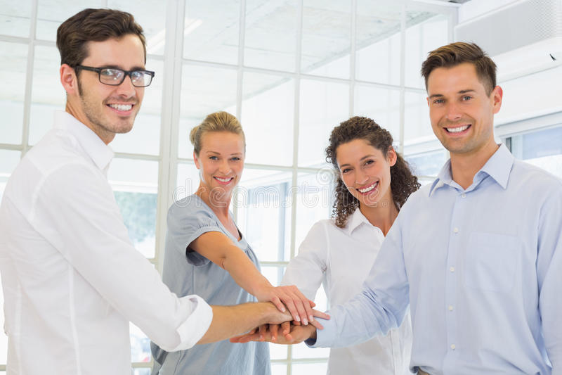 Toevallig glimlachend commercieel team die hun handen samenbrengen royalty-vrije stock foto