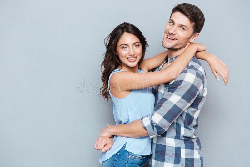 Toevallig jong paar die elkaar over grijze bakground koesteren royalty-vrije stock afbeelding
