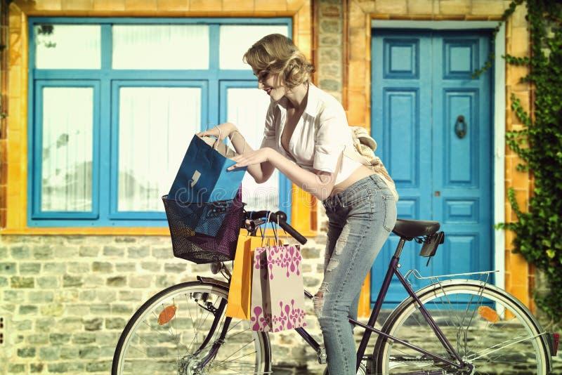 Toevallig meisje met byke en het winkelen zak stock afbeelding