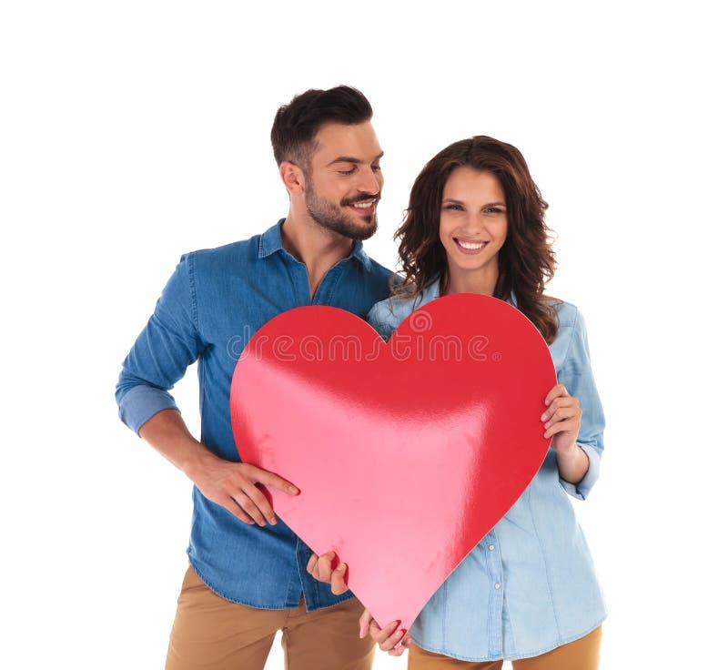 Toevallig paar die een groot rood hart tonen stock fotografie