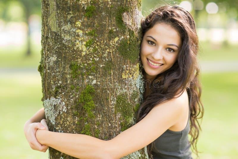 Toevallig vrolijk brunette die een boom omhelzen die camera bekijken stock afbeeldingen