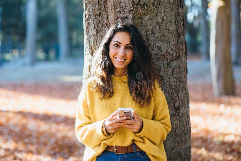 Toevallig vrouwenoverseinen op slimme telefoon in de herfst stock foto