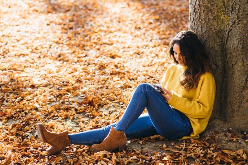 Toevallig vrouwenoverseinen op slimme telefoon in de herfst royalty-vrije stock fotografie