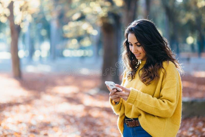 Toevallig vrouwenoverseinen op smartphone in de herfst royalty-vrije stock fotografie