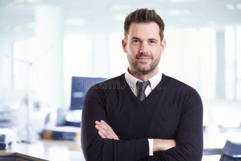 Toevallig zakenmanportret terwijl status in het bureau met gevouwen wapens stock foto's