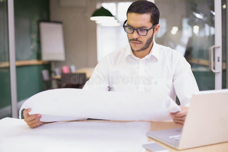 Toevallige architect die zijn blauwdrukken bestuderen stock afbeelding