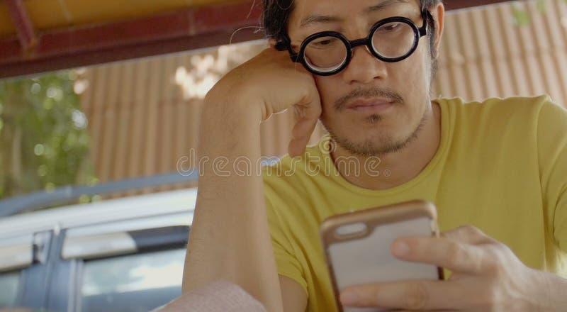 Toevallige Aziatische mens die smartphone gebruiken het controleren van post, praatjes royalty-vrije stock foto's