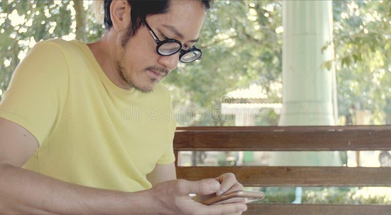 Toevallige Aziatische mens die smartphone gebruiken het controleren van post, praatjes royalty-vrije stock afbeeldingen