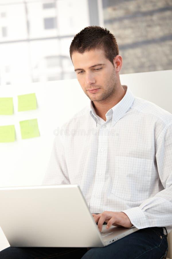 Toevallige beambte die laptop met behulp van stock foto's