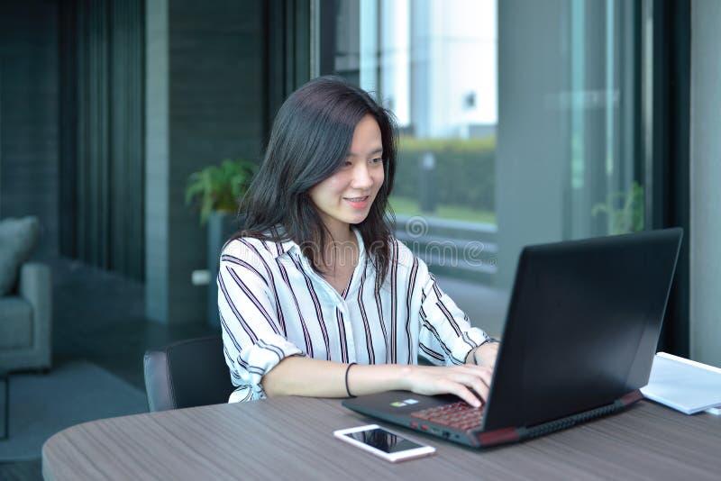 Toevallige Bedrijfs Aziatische Vrouw die en laptop in flatgebouw met koopflats glimlacht met behulp van stock afbeeldingen