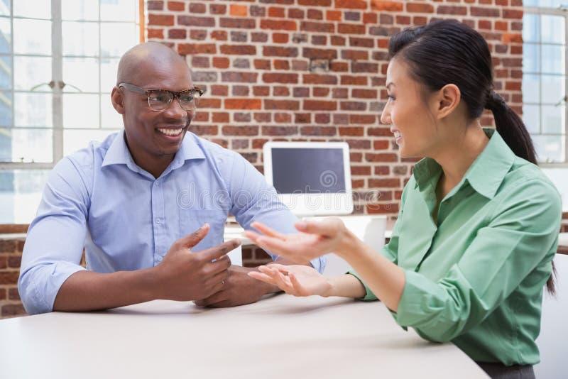 Toevallige bedrijfsmensen die bij bureau en het glimlachen spreken stock afbeeldingen