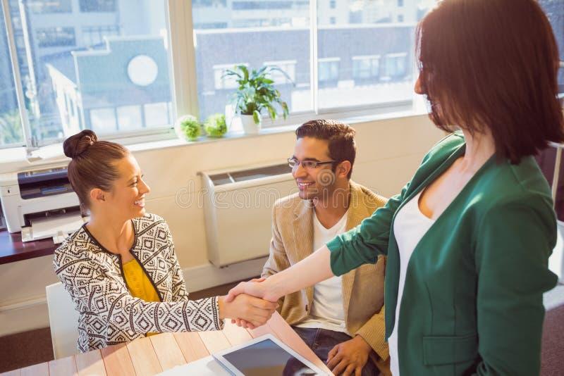 Toevallige bedrijfsmensen die handen schudden bij bureau en het glimlachen royalty-vrije stock foto