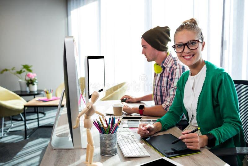 Toevallige collega's die grafische tablet en computer met behulp van stock afbeelding