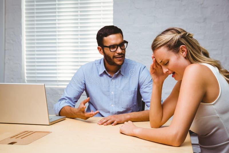 Toevallige collega's in een argument bij bureau stock afbeelding