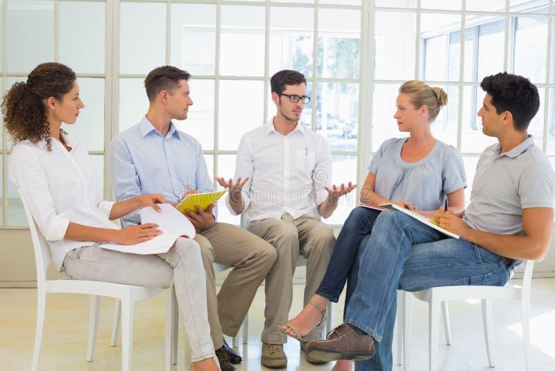 Toevallige commerciële teamzitting in een cirkel die een vergadering hebben stock foto