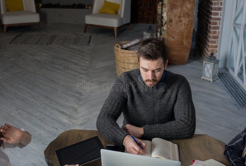 Toevallige geklede hipster kerel die in handboek tijdens trainingscursussen schrijven Student het leren royalty-vrije stock fotografie