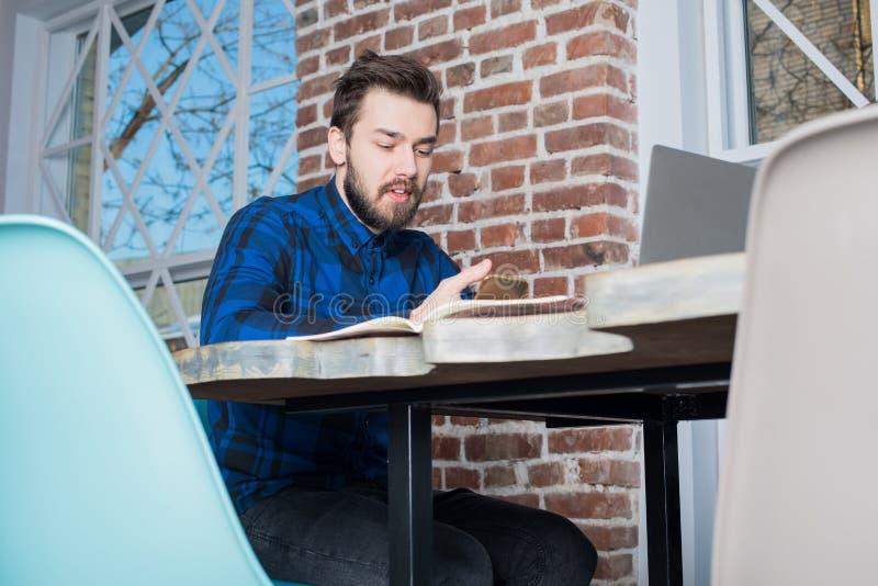 Toevallige geklede hipster kerel die op cellphone tijdens leren babbelen online op netto-boek royalty-vrije stock afbeelding
