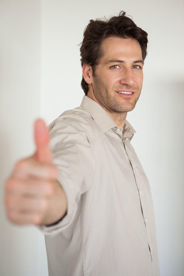 Toevallige glimlachende zakenman die duimen tot camera tonen stock foto's