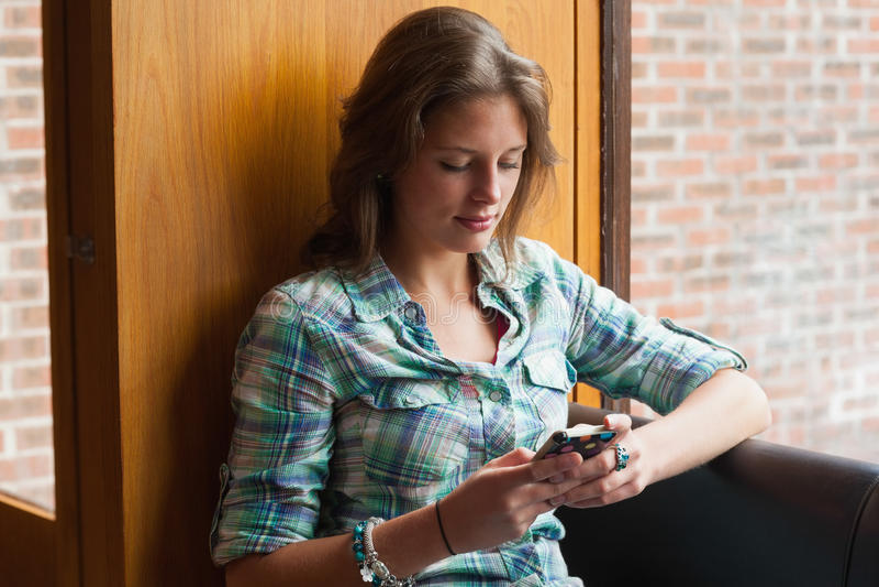 Toevallige het glimlachen studentenzitting naast venster het texting royalty-vrije stock afbeelding