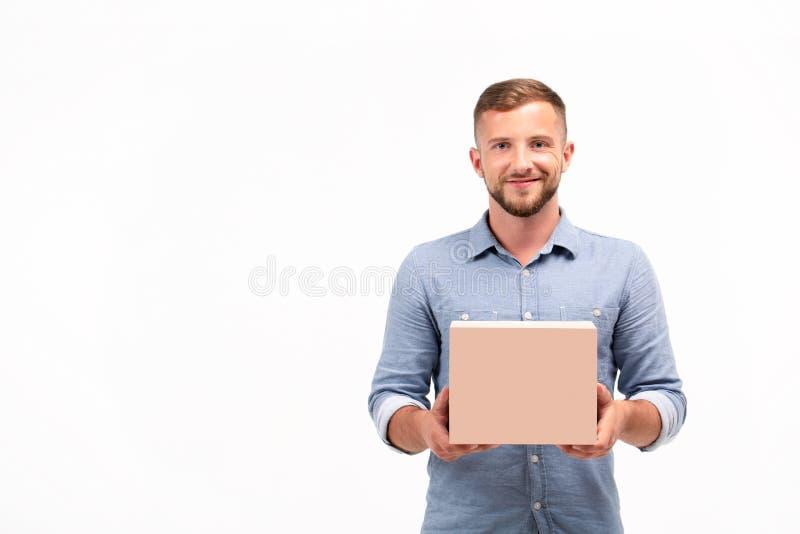 Toevallige jonge mens die een doos houden die op een witte achtergrond wordt geïsoleerd stock foto