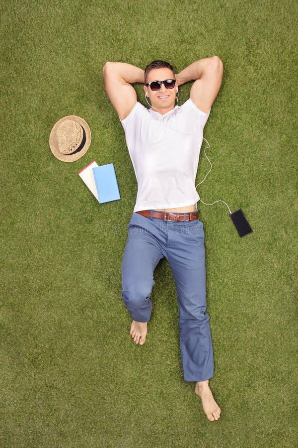 Download Toevallige Jonge Mens Die In Gebied Liggen En Aan Muziek Luisteren Stock Afbeelding - Afbeelding bestaande uit gras, muziek: 54079739