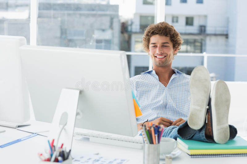 Toevallige jonge mens met benen op bureau in helder bureau royalty-vrije stock afbeelding