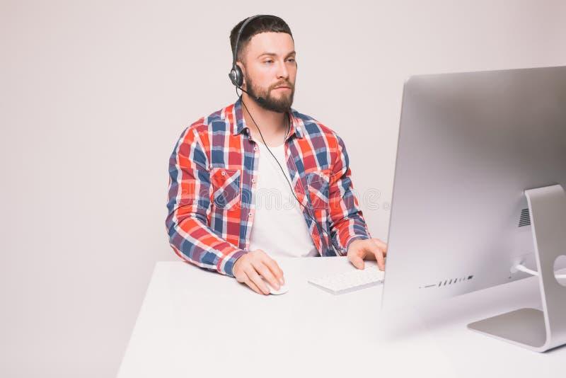 Toevallige jonge mens met hoofdtelefoon die computer in een helder bureau met behulp van royalty-vrije stock foto's