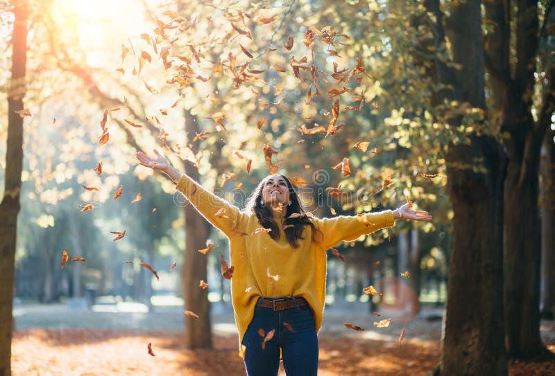 Toevallige jonge vrouw die de herfst van seizoen genieten bij stadspark royalty-vrije stock afbeeldingen