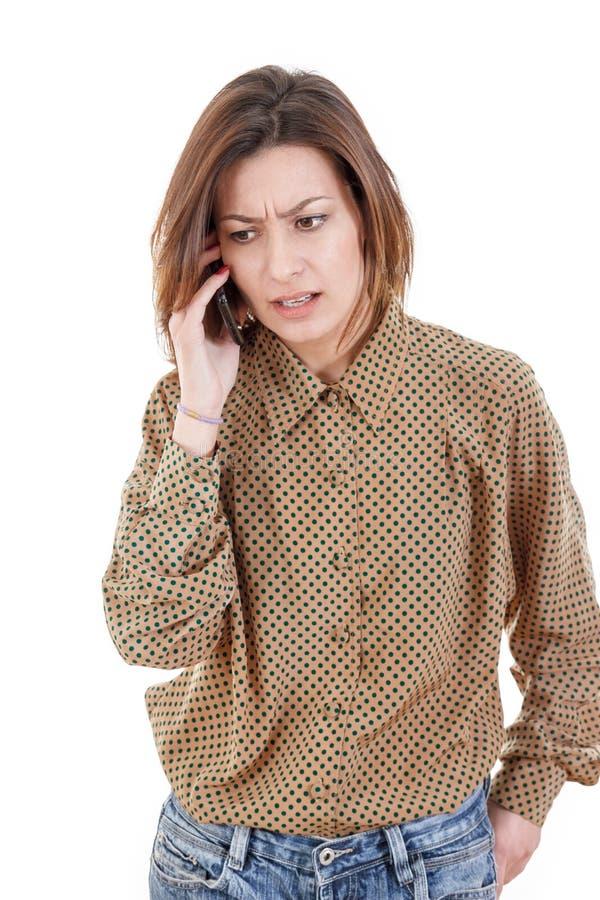 Toevallige jonge vrouw die op de telefoon spreken die slecht nieuws horen stock afbeelding