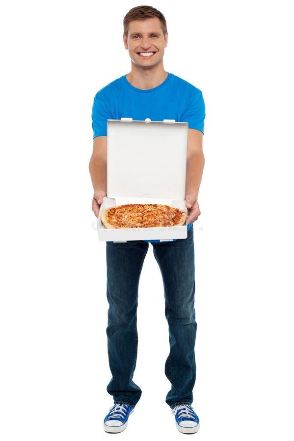 Toevallige kerel die vers gebakken yummy pizza toont royalty-vrije stock foto