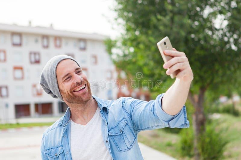 Toevallige manierkerel die een foto met mobiel in de stad nemen stock afbeeldingen