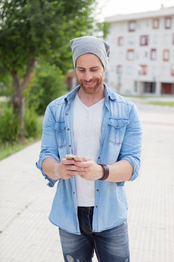 Toevallige manierkerel die een gang met zijn mobiel nemen stock foto