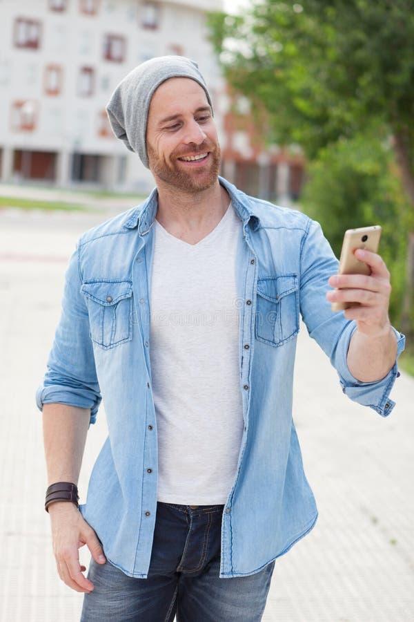 Toevallige manierkerel die een gang met zijn mobiel nemen stock afbeeldingen
