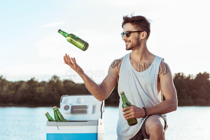 Toevallige mens die terwijl het jongleren van met flessen bier op rivieroever glimlachen stock afbeeldingen