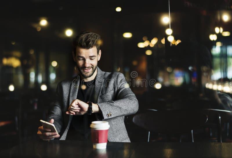 Toevallige mens die zijn horloge in de koffie bekijken stock foto's
